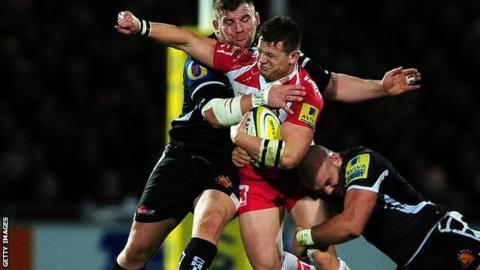 Darren Dawiduik of Gloucester is tackled by Moray Low and Jack Yeandle of Exeter