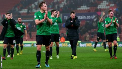 Wrexham players applaud the fans after their FA Cup third-round defeat at Stoke City