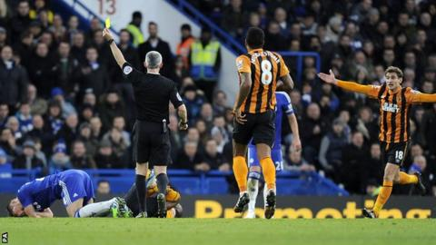 Chris Foy shows Chelsea defender Gary Cahill a yellow card against Hull