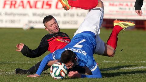 Tobermore United's Marc Harkness slides in as Linfield striker Andrew Waterworth takes a tumble at Fortwilliam Park