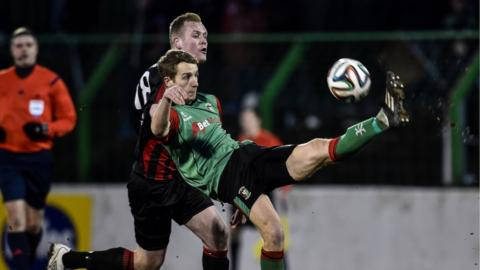 Glentoran's Johnny Addis tries to clear the danger as Jordan Owens closes in during Crusaders' 2-1 victory at the Oval