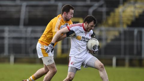 Antrim's Emmet Killough challenges Tyrone's Barry Tierney for possession during the McKenna Cup game which was moved to Clones