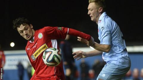 Cliftonville midfielder Tomas Cosgrove shields the ball from Ballymena's Stephen McBride