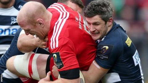 Munster's Paul O'Connell is tackled by Mark Easter and Tom Brady of Sale