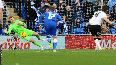 Cardiff goalkeeper Simon Moore saves Derby striker Chris Martin's penalty