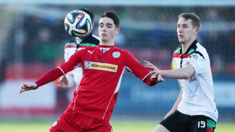 Jay Donnelly shields the ball from Johnny Addis as Cliftonville draw 1-1 with Glentoran at Solitude