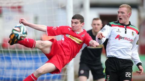 New Cliftonville signing Caoimhin Bonner clears the ball as Steven Gordon of Glentoran prepares to pounce