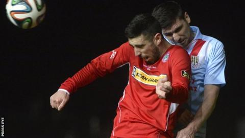 Cliftonville striker Joe Gormley and Ballymena's Davy Munster contest a high ball