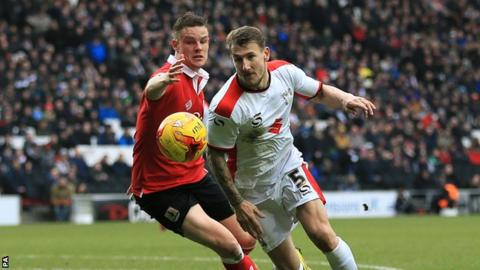 Bristol City's Matt Smith (left) and Mk Dons' Kyle McFadzean battle for the ball