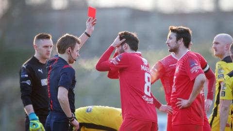 Portadown players Sean Mackle and Michael Gault react after referee Tim Marshall sends off their team-mate Gary Twigg during the second half of the 2-0 defeat by Cliftonville