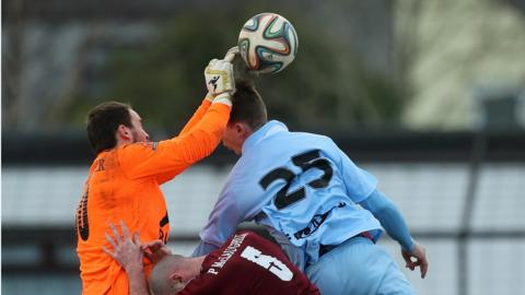 Institute goalkeeper Marty Gallagher rises to clear the ball as Ballymena substitute Matthew Shevlin attempts to get in a header
