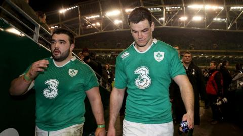 Ireland replacement prop Marty Moore leaves the field with Jonny Sexton after the hard-fought win over France