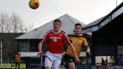 Newport County's Miles Storey and Shaun Beeley of Morecambe in action