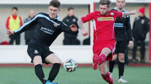 Ballymena United's Paddy McNally saw his clearance charged down by Cliftonville midfielder James Knowles at Solitude