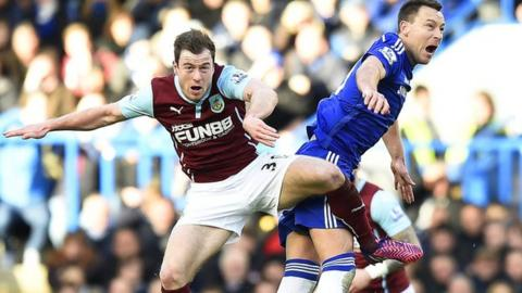 Burnley forward Ashley Barnes (left) goes up for a challenge with Chelsea captain John Terry