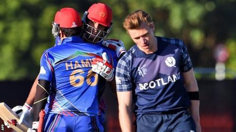 "Afghanistan batsmen Hamid Hassan (L) and Shapoor Zadran (C) celebrate as Scotland""s Richie Berrington (R) reacts"