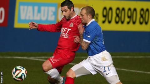 Keith O'Hara is challenged by Warren Feeney in Portadown 2-1 win at Windsor Park