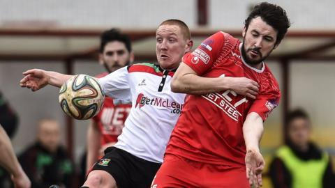 Stephen McAlorum of Glentoran and Portadown's Michael Gault in action during the 1-1 draw at Shamrock Park