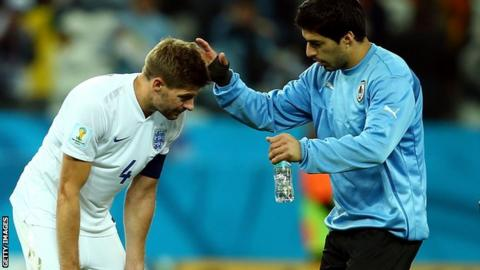 Luis Suarez comforts England's Steven Gerrard