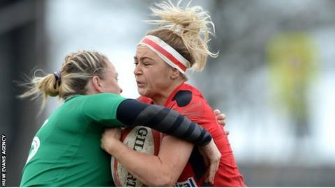 Adi Taviner of Wales is tackled by Niamh Briggs in Swansea