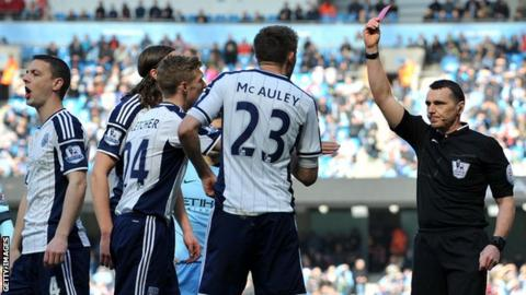 Referee Neil Swarbrick shoes a red card to the wrong player during the Manchester City-West Brom game