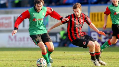 Glentoran's Fra McCaffrey in possession as Crusaders opponent Nathan Hanley moves in to challenge during the Irish Cup semi-final