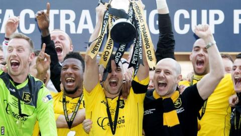 Livingston players celebrate as they lift the Petrofac Training Cup
