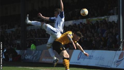 Craig Jones of Bury collides with Miles Storey of Newport County