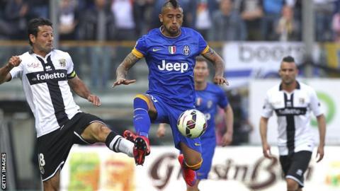 Parma players tackling Juventus' Vidal