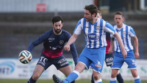 Ballinamallard's Johnny Lafferty looks on as Ruaidhri Higgins passes the ball for Coleraine at Ballycastle Road