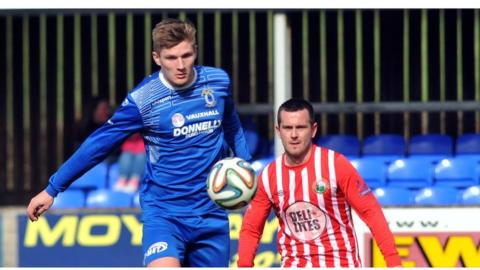 Dungannon's Andy Mitchell challenges for the ball with Warrenpoint's Mark Hughes during Saturday's Premiership game