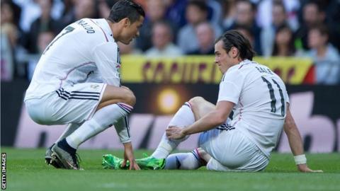 Concerned Real Madrid team-mate Cristiano Ronaldo checks on Gareth Bale's injury