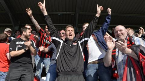 Crusaders manager Stephen Baxter joined supporters to celebrate winning the Irish Premiership after the 2-0 win over Glentoran at Seaview