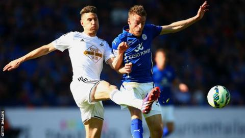 Angel Rangel of Swansea City and Jamie Vardy of Leicester City compete for the ball