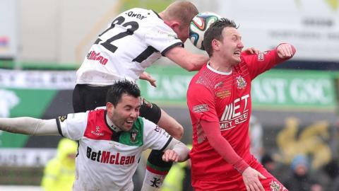 Glentoran's Niall Henderson and Steven Gordon compete for a high ball with Gary Twigg of Portadown