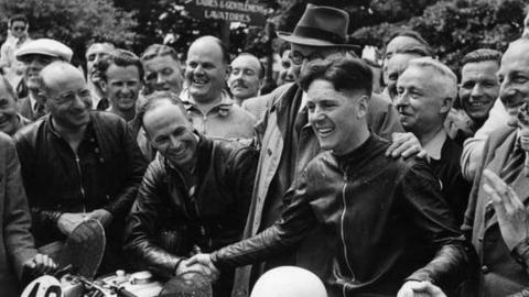 Well-wishers congratulating motorcyclist Geoffrey Duke on his victory in the Isle of Man Tourist Trophy Race (1950)