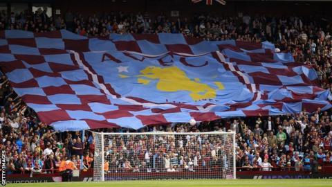 Aston Villa fans hold aloft a flag