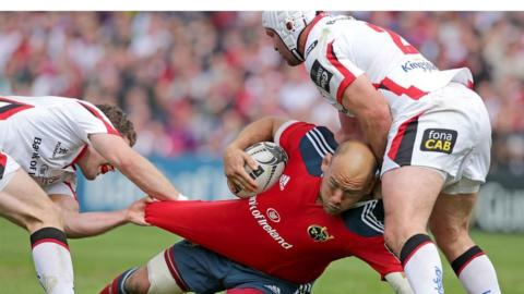 Munster prop BJ Botha is brought to ground by Rory Best and Darren Cave