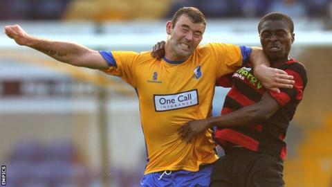 Mansfield's Matt Rhead challenges Peterborough United's Gabriel Zakuani