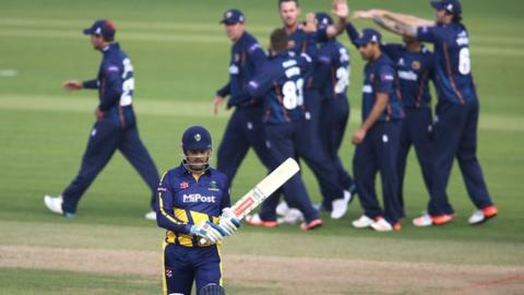 Essex celebrate in the background as Glamorgan's Jacques Rudolph walks back to the pavilion