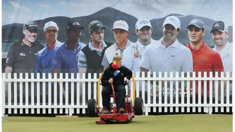 A groundsman puts the final touches to a putting green under the watchful gaze of some of the tournament's star players