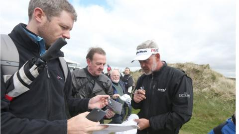 Darren Clarke signs autographs for fans during practice at the Newcastle course