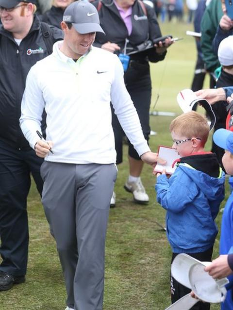 Irish Open event host and world number one golfer Rory McIlroy signs an autograph for a young fan before Wednesday's Pro-Am