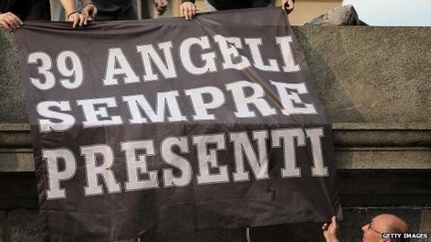 "Juventus supporters hold a banner reading ""39 angels forever"" outside the Gran Madre di Dio church in Turin"