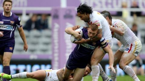 Giants back row forward Jack Hughes is held up by Catalan Dragons' Zeb Taia