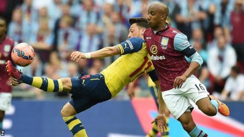 Fabian Delph competes with Arsenal's Mesut Ozil at Wembley