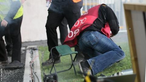 Photographer Daren Kidd falls after being struck during the match at Windsor Park