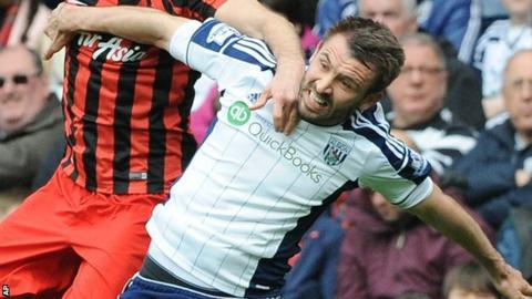 Gareth McAuley challenges for an aerial ball with Clint Hill