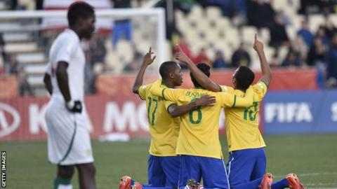 A Senegal player stands dejected as Brazil's players celebrate