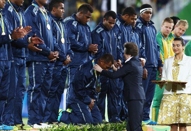 The Fiji players, renowned for both their humility and size, kneel to receive their medals from the Princess Royal